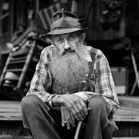 Legendary moonshiner Popcorn Sutton sits on his front porch.