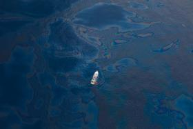 A ship floats amongst a sea of spilled oil in the Gulf of Mexico after the BP Deepwater Horizon oil spill disaster. (2010)