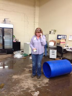 Dee Dee Flounlacker takes a call from a community leader in the flood damaged offices of Manna Food Pantry
