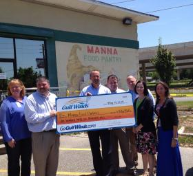 Chris Rutledge, President and CEO of Gulf Winds Credit Union presents a check to Jay Bradshaw and Dee Dee Flounlacker of Manna Food Pantries.