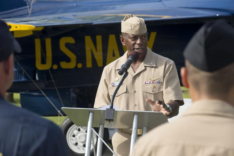 Naval Air Station (NAS) Pensacola Commanding Officer and former Blue Angel Solo Pilot, Capt. Keith Hoskins, speaks at an unveiling of a Blue Angels F/A-18 Hornet display at the entrance of NAS Pensacola. The unveiling celebrated the base's 100th anniversa