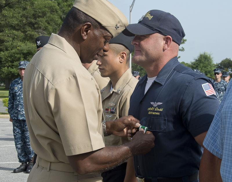 ) Naval Air Station (NAS) Pensacola Commanding Officer and former Blue Angel Solo Pilot, Capt. Keith Hoskins, pins a Navy and Marine Corps Commendation Medal onto Aviation Structural Mechanic 1st Class Brandon Dodd, a member of the Blue Angels maintenance