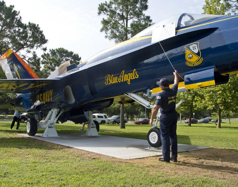 Aviation Structural Mechanic 1st Class Brandon Dodd, a member of the Blue Angels maintenance team, helps unveil the new Blue Angels F/A-18 Hornet display at the entrance of Naval Air Station Pensacola during a ceremony celebrating the base's 100th anniver