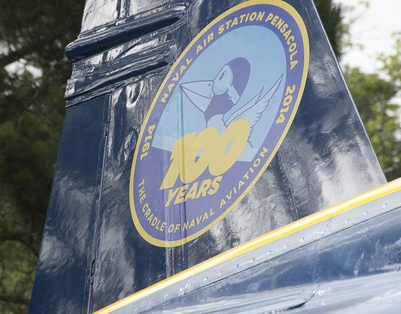 The new 100 Years of Naval Air Station (NAS) Pensacola crest is revealed on the vertical stab of the Blue Angels F/A-18 Hornet display at the entrance of NAS Pensacola celebrating the base's 100th anniversary. The freshly painted Hornet served on the Blue