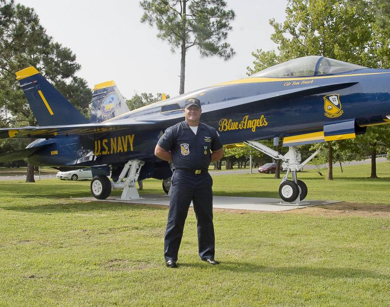 ) Aviation Structural Mechanic 1st Class Brandon Dodd, a member of the Blue Angels maintenance team, poses for a photo in front of the new Blue Angels F/A-18 Hornet display at the entrance of Naval Air Station (NAS) Pensacola. The F/A-18 Hornet was unveil
