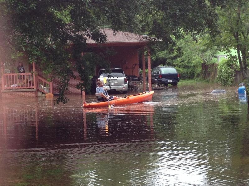 Someone kayaking the floodwaters in Santa Rosa county