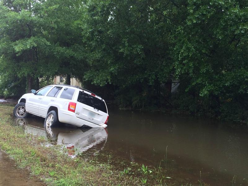 Car moved by floodwater into a roadside ditch.