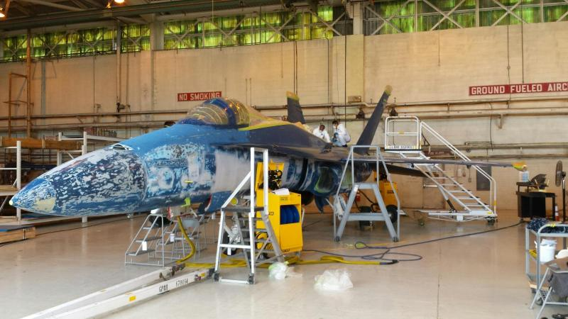 Sailors volunteer on a restoration team to re-paint a former Blue Angel F/A-18 Hornet at the National Naval Aviation Museum to prepare it for display at the entrance of Naval Air Station Pensacola. The aircraft served on the Blue Angels team from 1991 to