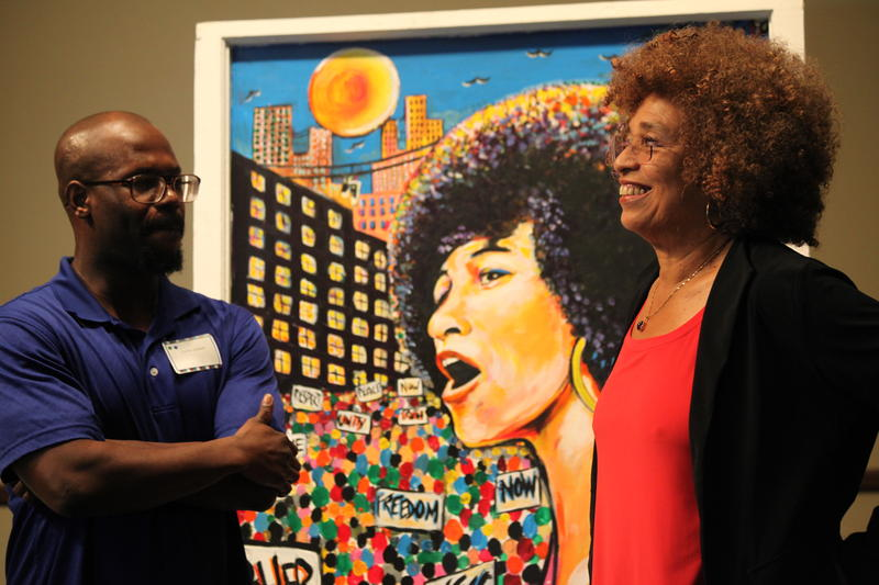 Carter J and Dr. Angela Davis talk in front of painting by Carter J at the 14th Annual UWF Women's Studies Conference