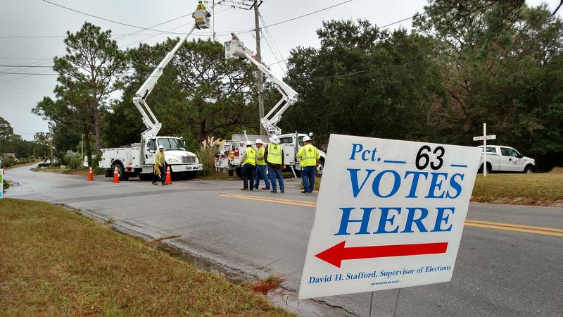 Gulf Power crews work to restore electricity near Precinct 63 after a transformer blows.