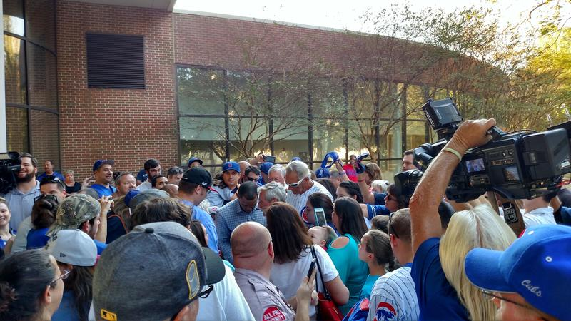 Addison Russell is surrounded by local fans seeking autographs and photos.