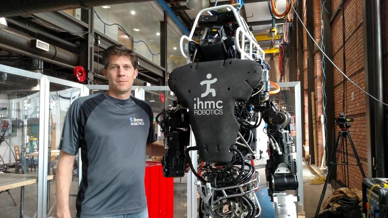 IHMC researcher Dr. Matt Johnson alongside the Boston Dynamics Atlas robot on display at the IHMC Robotics Lab.