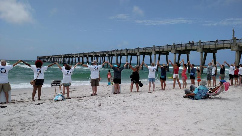 Area residents wrap up the annual Hands Across the Sand event Saturday on Pensacola Beach.