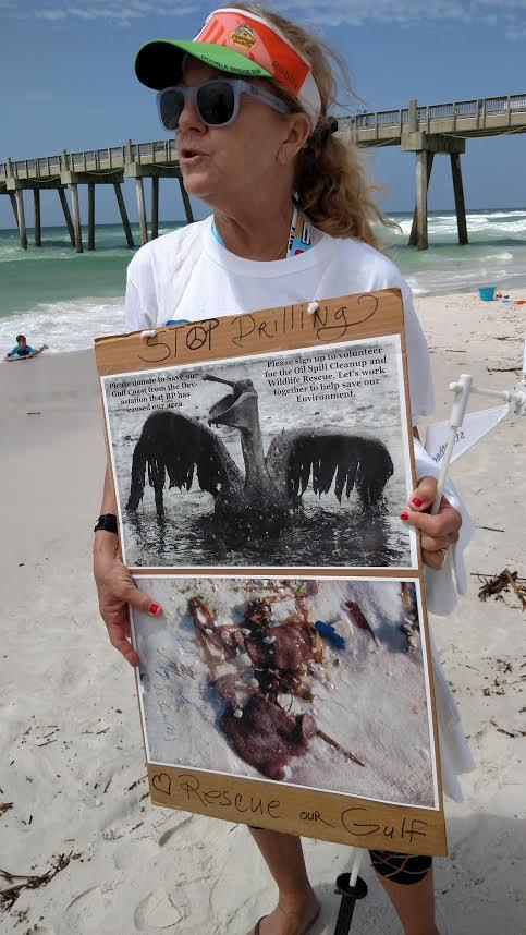 Pensacola Beach resident Monie Russo shows off a sign showing damage from the BP-Deepwater Horizon Oil Spill.