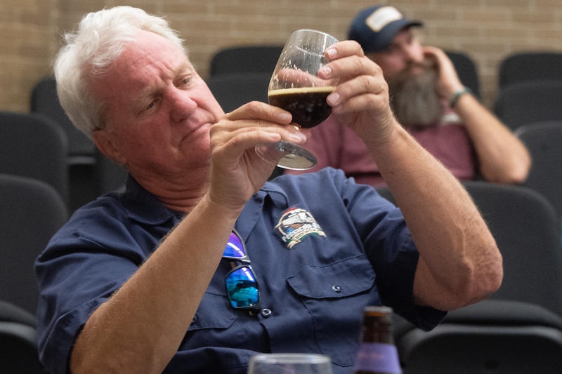 Judge Mark Robertson of Pensacola Bay Brewery tastes Abigail Megginson's beer Abigail Adams American Milk Stout during the University of West Florida Kugelman Honors Program Art and Science of Brewing class tasting competition Wednesday April 25,