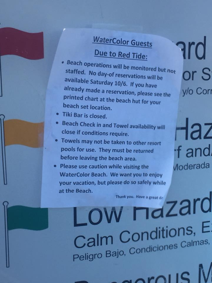 A sign alerts beachgoers of red tide.