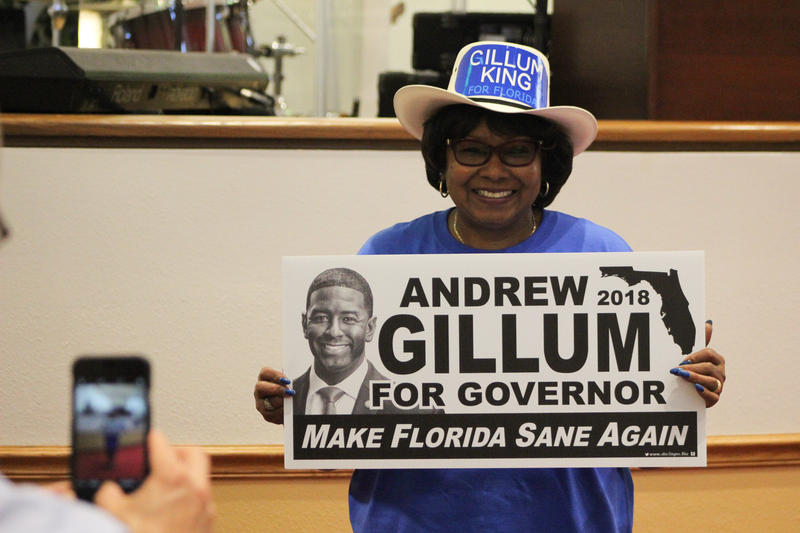 A woman smiles with her Andrew Gillum yard sign.