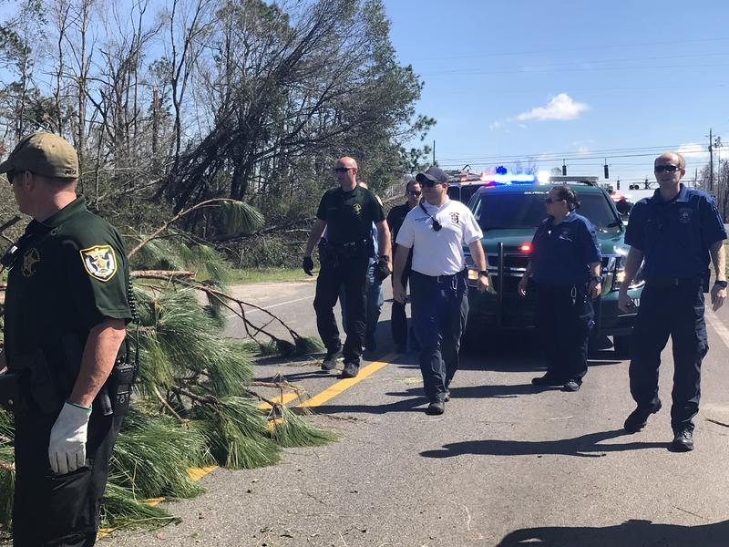 Members of a response team from Escambia County prepare to clear storm debris from a roadway in Bay County.