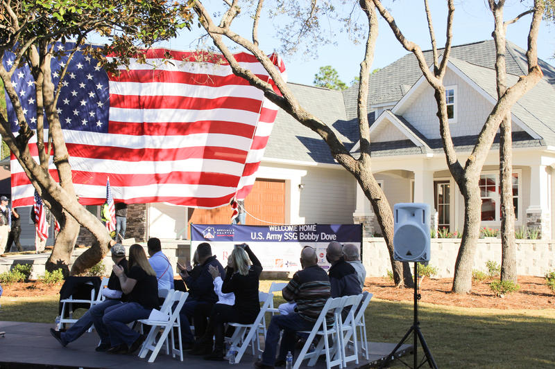 People clap and cheer as an American flag reveals the Dove family home.