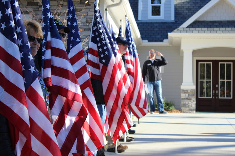 A motorcycle crew line the driveway with American flags.