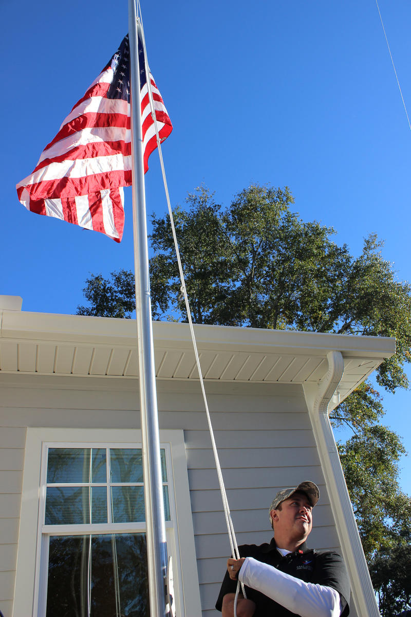 Bobby Dove raises the American flag at his new home