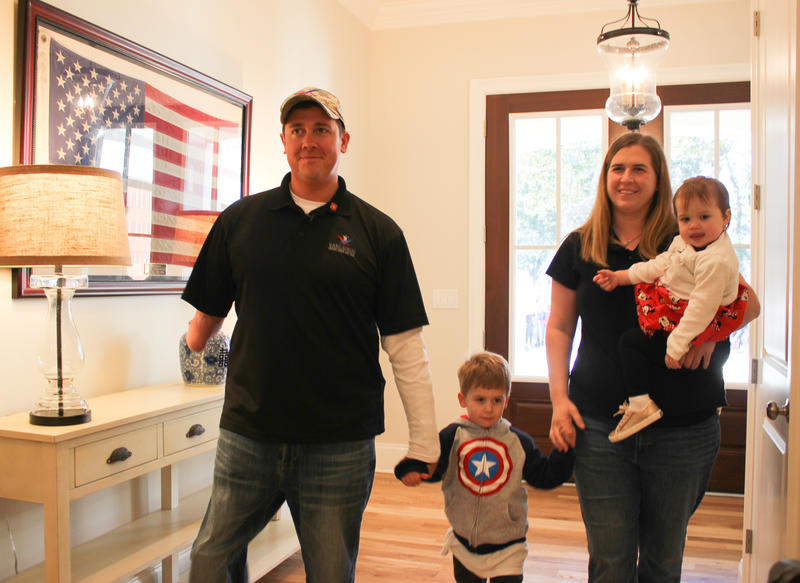 Dove and his wife, Mary-Elizabeth and their children, Wyatt and Eva, step inside their new home in Bluewater Bay after a home dedication ceremony Wednesday.