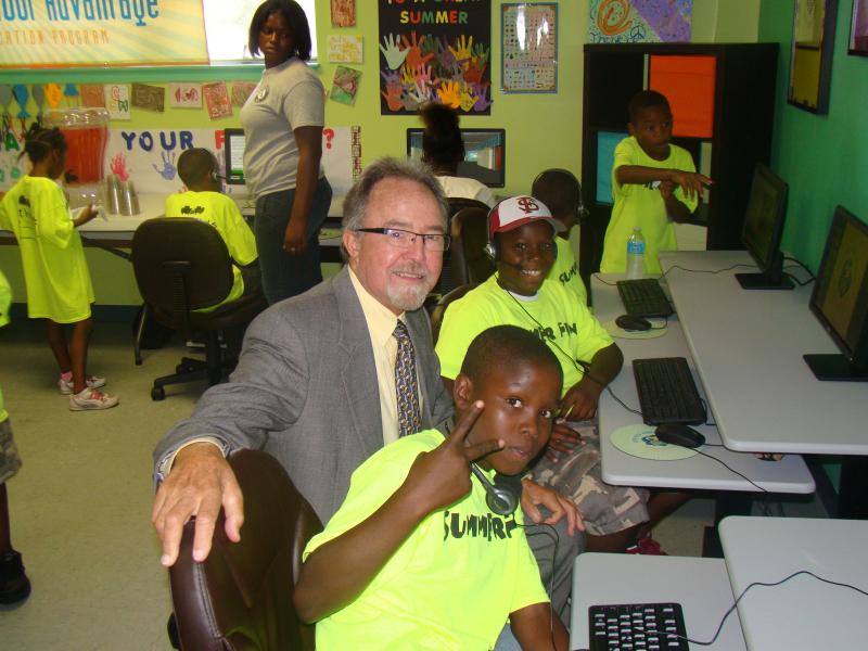 Florida Lottery District Manager Mike Mabry smiles with a couple of members at the grand opening of GTECH's 238th worldwide After School Advantage computer lab at Pathways For Change in Pensacola.