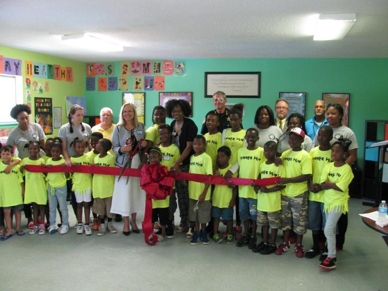 Executive Director of Pathways For Change, Inc. Connie Bookman officially cuts the ribbon on the newly donated GTECH After School Advantage lab at its grand opening. Joining her are staff and students of Pathways For Change, along with Chaplain & Director