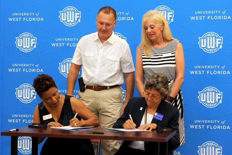 UWF President Dr. Judy Bense signing the partnership with Alicia Booker, President of the Crestview Area Chamber of Commerce. (standing behind- Crestview Chamber Executive Director Wayne Harris and Marian McBryde President-Elect, Crestview Area Chamber of
