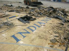 Workers tear up the gym floor bearing the Indians nickname.