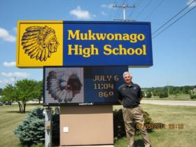 Mukwonago High School Principal Shawn McNulty stands near the sign on the lawn.