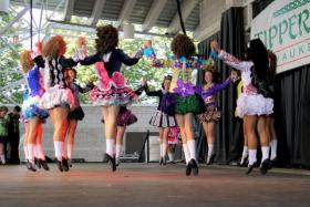 Rince Nia dancers at Irish Fest, wearing the trademark colorful dresses and curly wigs of Irish dance.