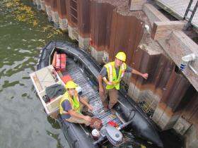 A crew moves along the Milwaukee River fastening floating aquatic plant baskets to sheet piling.