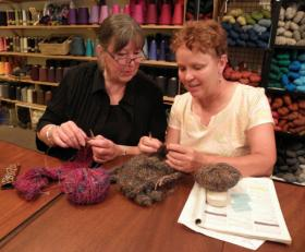Instructor Pat Barry (left) helps a student with a project at one of Fiberwood Studio's open knitting classes.