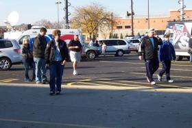 TV trucks and bystanders filled the parking lot at Brookfield Square, across from Sunday's shootings at the Azana Salon