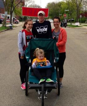 Addie, her parents and her older sister, participating recently in a Whitefish Bay community run. The family is pleased with Addie's public school education, and worries the special needs vouchers would drain resources from her school