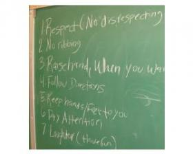 Words on a chalkboard spell out the code of conduct for the Peace Making Circle.