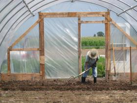Fondy Farm Project grower Brigid McGeehan prepares soil for planting in the new hoop house.