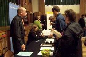 Dozens of job seekers speak with potential employers at a fair on Milwaukee's north side.