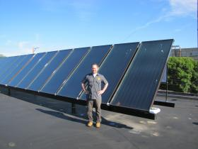 Jim McCabe shares rooftop with solar panels that heat water used in brewing process.