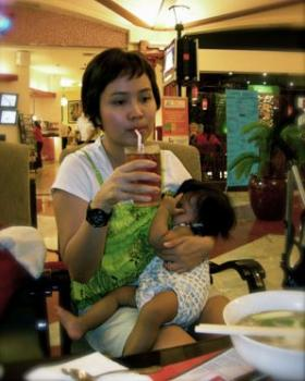 A mother breastfeeds her child at a restaurant.