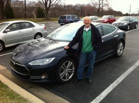 Lake Effect parental figure Al Teich, in front of his Tesla