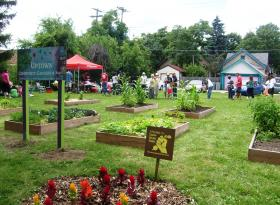 Several dozen people turned out at a community garden for a picnic and tree dedication organized by the Uptown Crossing Neighborhood Association.