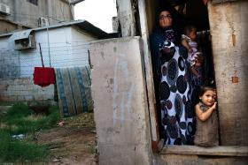 A Syrian refugee family from the Deir el Zour, Syria pauses in their doorway in a neighborhood with a high concentration of Syrian refugees in Beirut, Lebanon.
