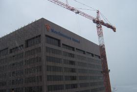 A tall crane is poised to take materials from the top of the building