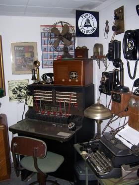 Another prized piece of Pat Carew's telephone collection is his still-operating switchboard (center).