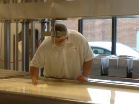 Juan Cruz checks on progress of cheese in the making.