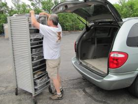 Chris Capper rolls the food tower outside and slides tray upon tray into his van.