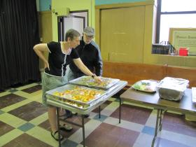 Pastor Donna Brown and volunteer Mark Petersen inspect newly arrived fruit kabobs.