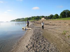 While Lenz gathers water samples; colleague Nusrat Shaik (right) enters beach environment data on iPad.